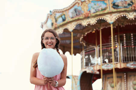 Young woman with cotton candy in amusement park. Space for text
