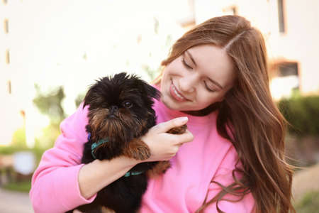 Young woman with adorable Brussels Griffon dog outdoors Фото со стока