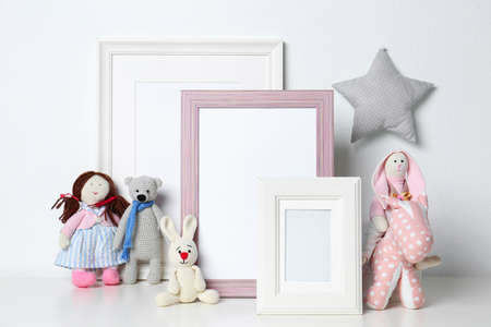Soft toys and photo frames on table against white background, space for text. Child room interior Stock Photo