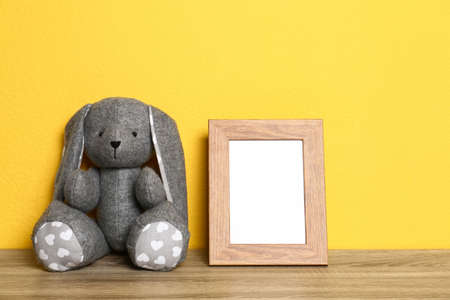 Empty photo frame and and soft rabbit on wooden table against yellow background, space for text. Child room interior