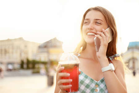 Young woman with refreshing drink talking on phone outdoors. Space for text