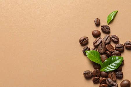 Frische grüne Kaffeeblätter und Bohnen auf hellorangefarbenem Hintergrund, flach. Platz für Text