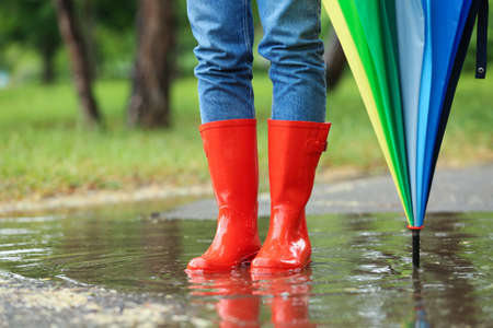 Woman with umbrella and rubber boots in puddle, closeup. Rainy weather