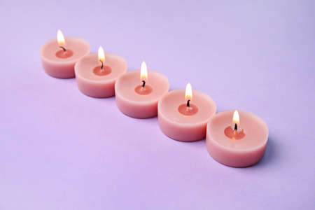 Burning wax decorative candles on purple background