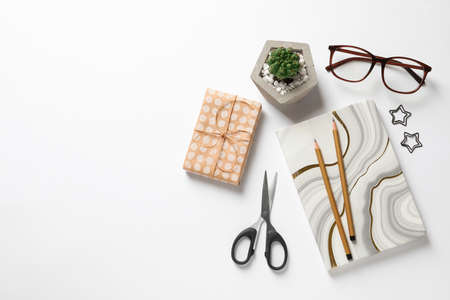 Composition of scissors, notebook and cactus on white background, top view