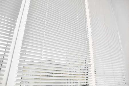 Window with modern horizontal blinds indoors, closeup