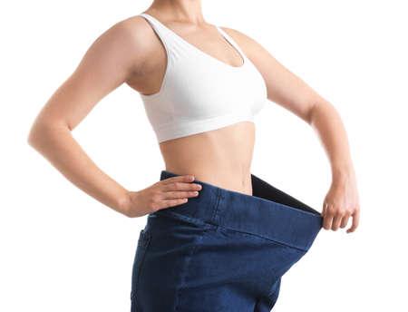 Joven mujer delgada vistiendo jeans de gran tamaño sobre fondo blanco, primer plano Foto de archivo
