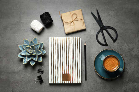 Flat lay composition with scissors, notebook and coffee on grey table