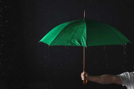 Man holding green umbrella under rain against black background, closeup