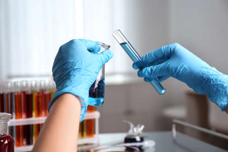 Scientist holding tube and conical flask at laboratory, closeup. Solution chemistry