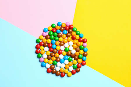 Delicious bright glazed candies on color background, top view
