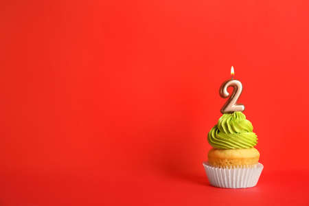 Birthday cupcake with number two candle on red background, space for text