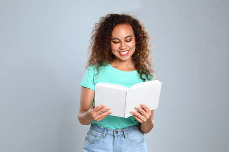 Beautiful African-American young woman reading book on light background