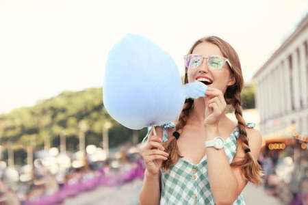 Young woman with cotton candy on city street. Space for text