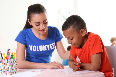 Petit garçon afro-américain apprenant l'alphabet avec un volontaire à table à l'intérieur