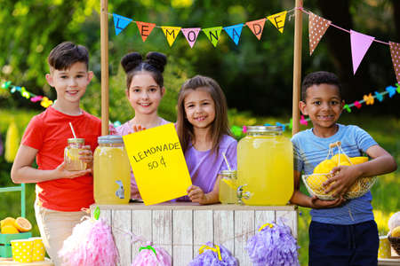 Cute little children at lemonade stand in park. Summer refreshing natural drink Фото со стока