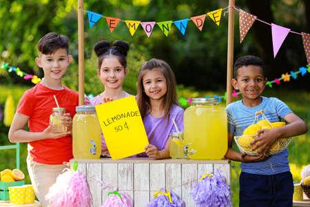 Nette kleine Kinder am Limonadenstand im Park Sommer erfrischendes Naturgetränk