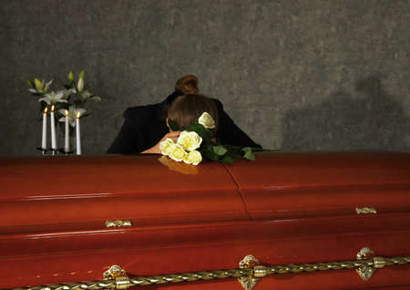 Sad woman mourning near casket with white roses in funeral home
