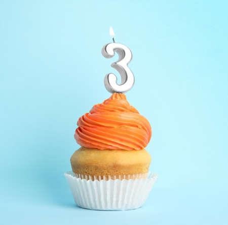 Cupcake de cumpleaños con vela número tres sobre fondo azul. Foto de archivo