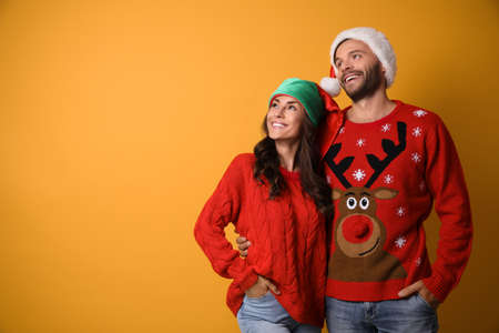 Young couple in Christmas sweaters and hats on yellow background. Space for text 版權商用圖片