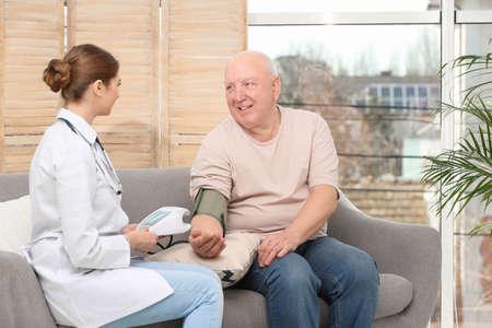 Nurse measuring blood pressure of elderly man in living room. Assisting senior generation