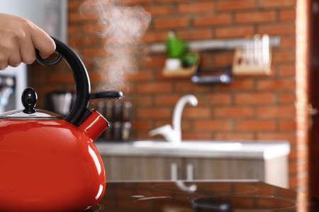 Woman holding modern kettle on stove in kitchen, closeup with space for text