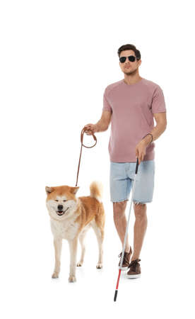 Blind man with walking stick and dog on leash against white background