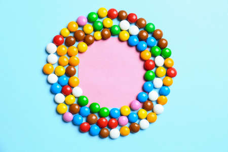 Frame made of delicious candies on color background, top view. Space for text