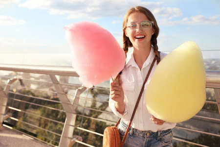Young woman with cotton candies outdoors on sunny day. Space for text