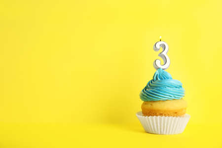 Birthday cupcake with number three candle on yellow background, space for text Archivio Fotografico