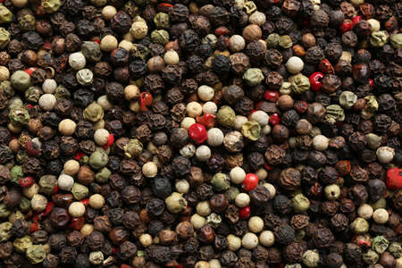 Many different peppercorns as background, top view
