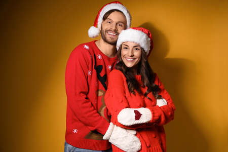 Young couple in Christmas sweaters and hats on yellow background 版權商用圖片