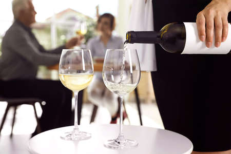 Waitress pouring wine into glass in restaurant, closeup Stockfoto