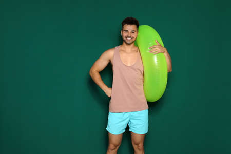 Funny young man with bright inflatable ring on dark green background, space for text