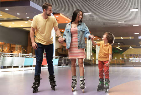 Happy family spending time at roller skating rink