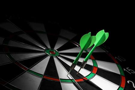 Flechas verdes que golpean el tablero de dardos contra el fondo negro. Espacio para texto