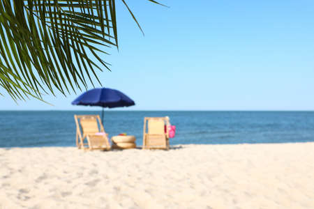 Wooden sunbeds and beach accessories on sandy shore Stock Photo