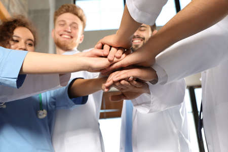 Team of medical workers holding hands together in hispital, closeup. Unity concept