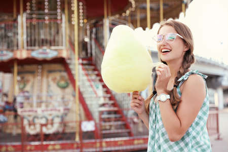 Young woman with cotton candy in amusement park. Space for text Banco de Imagens