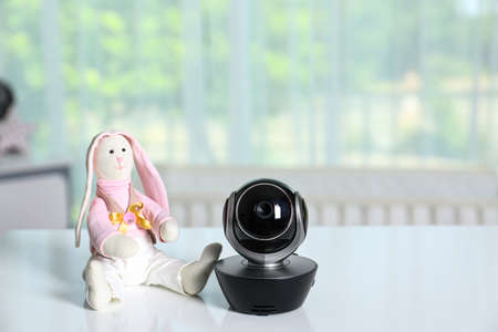 Baby camera with toy on table in room, space for text. Video nanny
