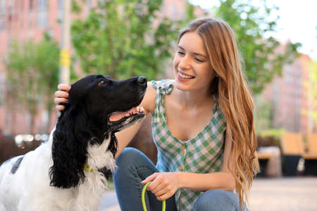 Young woman with her English Springer Spaniel dog outdoors