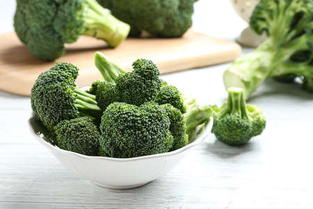 Plate of fresh green broccoli on white wooden table, closeup view. Space for text