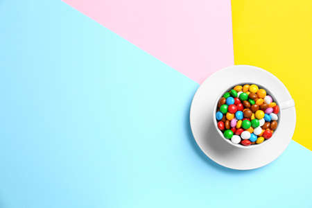 Cup with delicious bright glazed candies on color background, top view. Space for text