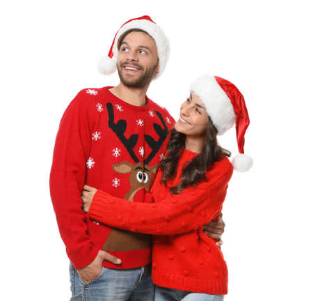 Young couple in Christmas sweaters and hats on white background