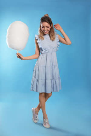 Full length portrait of pretty young woman with tasty cotton candy on blue background