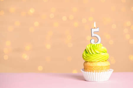 Birthday cupcake with number five candle on table against festive lights, space for text