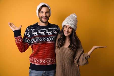 Young couple in Christmas sweaters and hats on yellow background 写真素材