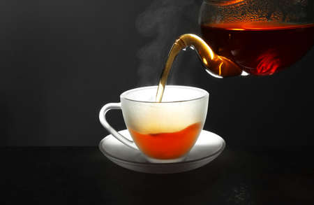 Pouring fresh hot tea into glass cup on table against grey background