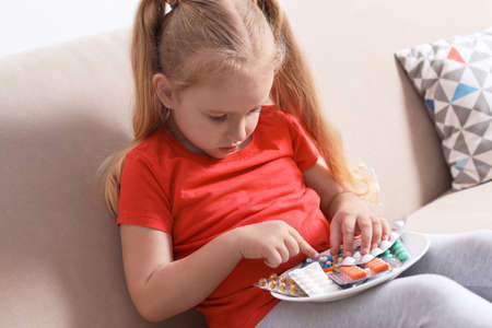Little child with plate of different pills at home. Household danger Stock Photo
