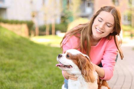 Mujer joven con adorable perro Cavalier King Charles Spaniel al aire libre